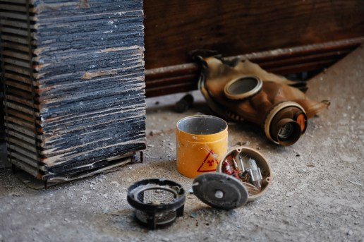 Detail image of a gas mask behind some radioactive components from a smoke alarm
