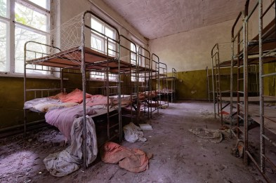 A small dormitory filled with rusty children bunk beds.