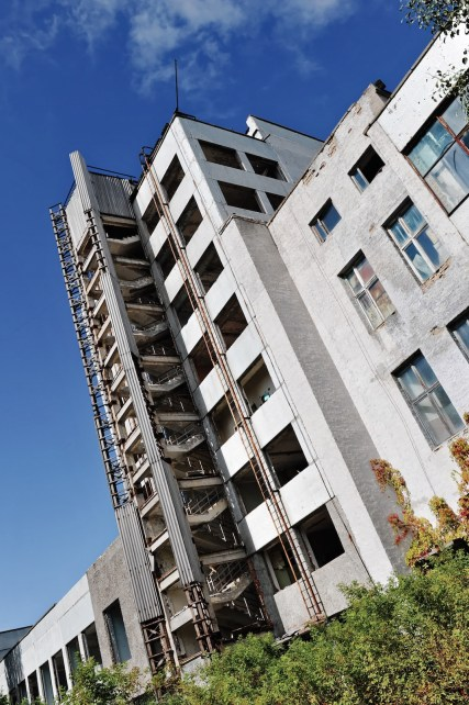 An exterior view of a six storey stairwell, angles up towards a blue sky.