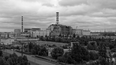 Elevated mono image showing a road in foreground and reactors 3 and 4 on horizon