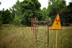 A crude radiation warning sign separates the viewer from an overgrown children's playground