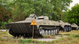 A tank-like tracked vehicle held stationery by a yellow radiation sign in a green space on it's own concrete plinth