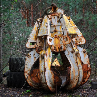 A rusty excavators claw sits detached by a pile of tyres at the edge of a copse of trees. A yellow radiation warning sign is just visible in front.