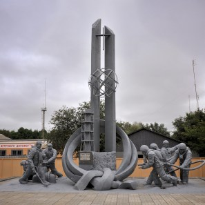 A basic but moving monument outside the fire station; a central column representing the reactor is flanked on both sides by life-size status of firefighters in action with various types of unusual equipment, their faces distorted by emotion.