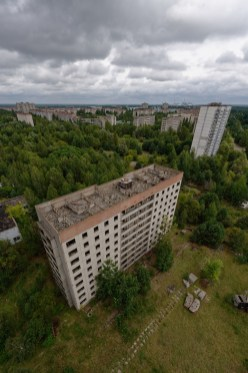 Elevated fisheye view of a tower block standing in overgrown Pripyat
