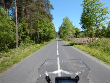 Onboard shot of a straight rural road under spotless blue sky