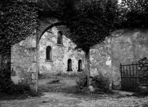 Square black and white image of ivy-covered gateway leading to Clifden Castle courtyard