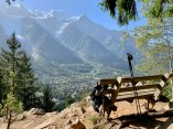 Hiking poles and backpack on a bench overlooking Chamonix alpine scene