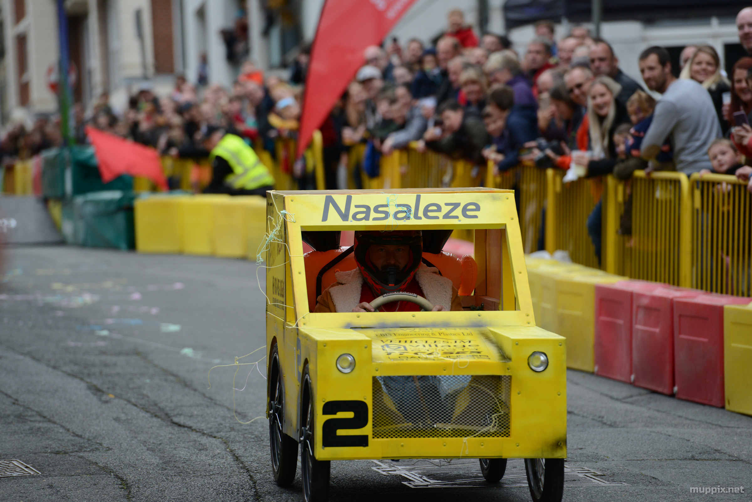 Action photo of a yellow soapbox cart going down the hill