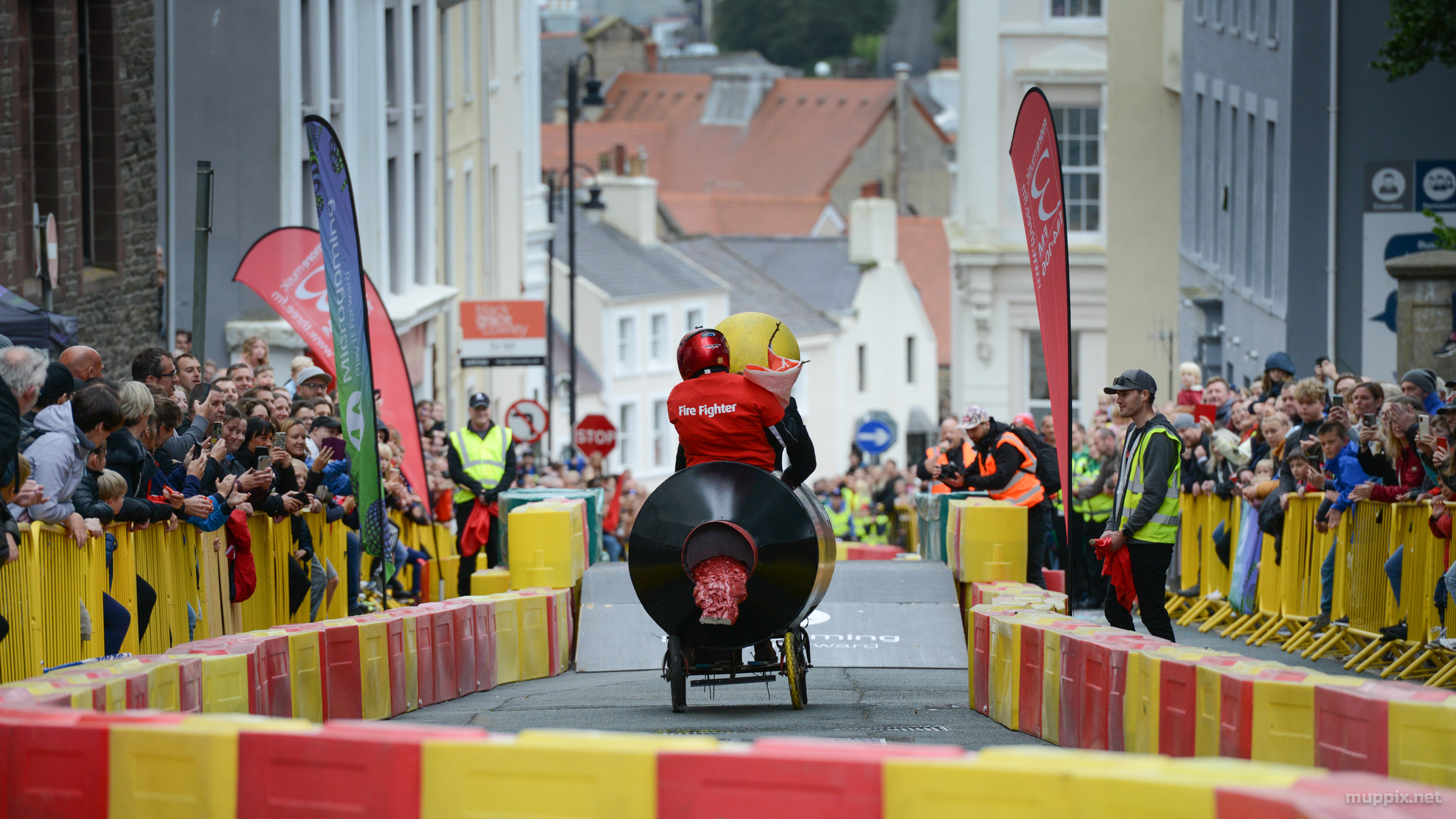 Back-end shot of a soapbox hurtling down a hilly street, crowds either side behind yellow barriers