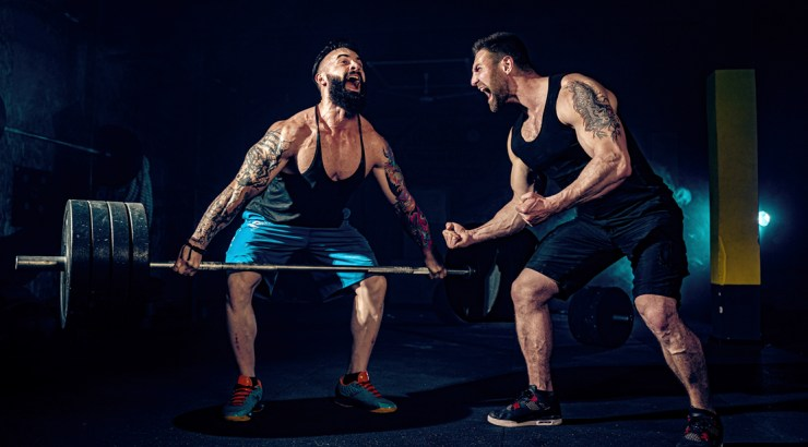 Muscular-Man-Deadlifting-Heavy-Weights-Struggling-workout-Partner motivating partner to get over his fitness plateau