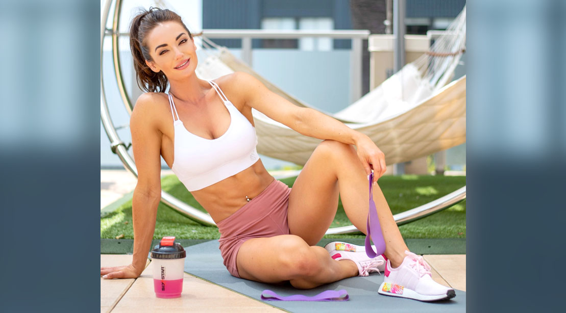 Fitness influencer Whitney Johns holding resistance bands for her great glutes workout
