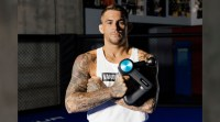 UFC and MMA fighter Dustin Poirier holding a massage gun from Therabody