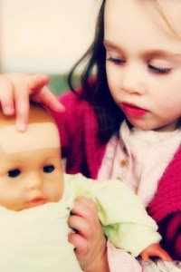 little-girl-putting-a-plaster-on-her-baby-doll