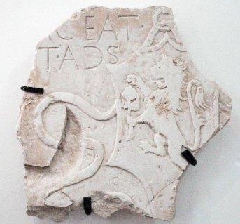 Frammento di lapide sepolcrale con stemma sforzesco, XV sec, marmo, cm 43x44/. Raffigura uno scudo a testa di cavallo sostenuto da un anello e decorato ai lati da due nastri. All'interno vi è effigiato a bassorilievo il leone rampante che regge il cotogno con la zampa sinistra e lo protegge con la destra.