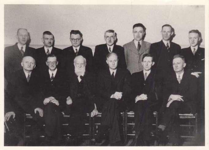 Op de voorste rij van links naar rechts: A. Lotman, A.C. v.d. Giessen, dominee F. Kramer, dominee H. Holtrop, N. Passchier en C. Slings. Staande van links naar rechts: J.P. Dekker, D. Willems, A. Mak, H.J. Tibboel, G.H. Teusink, G. Keizer en als laatste J.H. v.d. Schoor. Deze foto van predikanten en kerkeraad is uit 1936