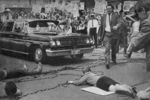 Anti-war protesters lie down in front of Presidential motorcade, 1966.