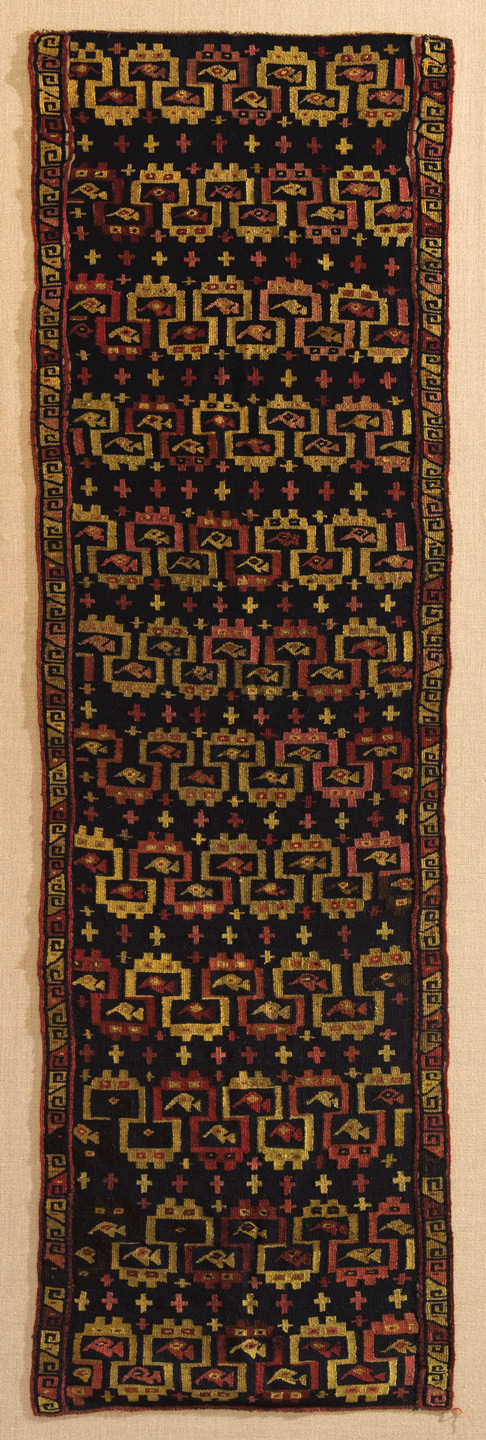 A textile decorated with a series of geometric, abstract feline heads. (Chancay)