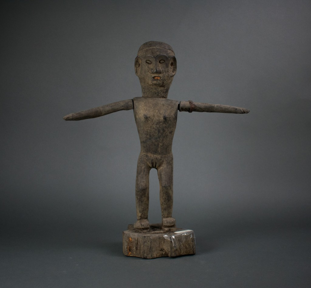 A wooden effigy of an ancestor with its arms outstretched