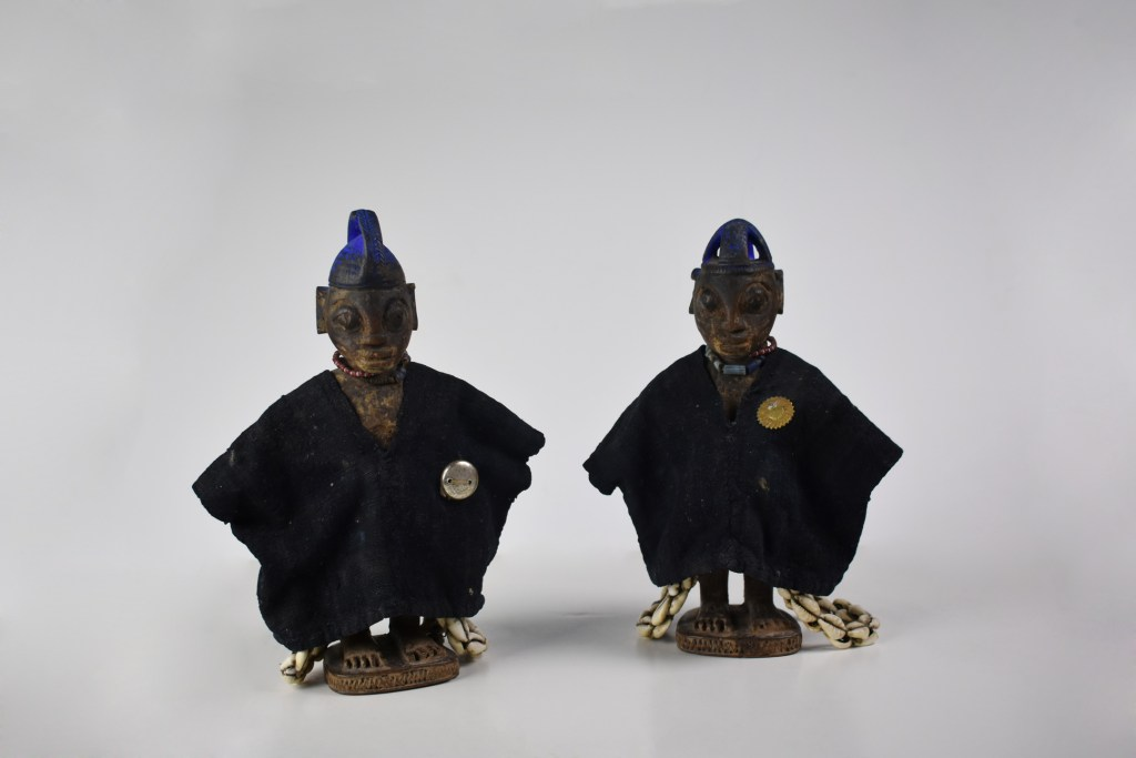 A pair of small, wooden human effigies from Nigeria known as Ere Ibeji