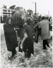 "Policeman and other man assisting female survivor from ""Wahine"", Seatoun Wharf"