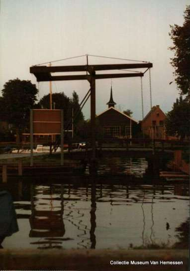 Comriekade brug over de voormalige wijk van boerderij Kroes. Aan de overzijde de houten noodkerk 1981 Noord West