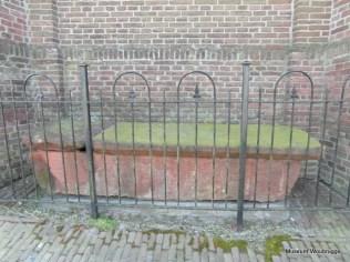 Sarcofaag. In een feestrede tgv het honderd jarig bestaan van de kerk in Oudshoorn vermeldt ds Pot de vondst (in 1743) van deze sarcofaag na de droogmaking van de Vierambachtspolder bij de fundamenten van de kerk van Jacobswoude. Dit soort sarcofagen dateert uit de, ruim te nemen, 12e eeuw. Na de vondst heeft de sarcofaag op verschillende plaatsen in Woubrugge gelegen: op het oude kerhof tegen de ZW-muur van de kerk, achter de gevangenis bij het gemeentehuis en nu dus tegen de N-muur van de kerk.