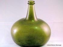 """Groen """"Kattekop"""". Fles gevonden door Dirk Bik in zijn achtertuin (nu Batehof). 1560-1700. Schenking H. van Berkel."""