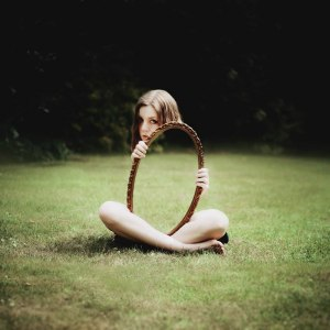 woman-holding-mirror-on-grass-reflection by LAURA WILLIAMS