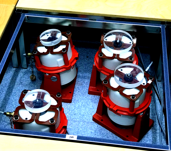 Closeup showing four red vibrotactile foot shakers in the square hole in the middle of the musical vibrations stage