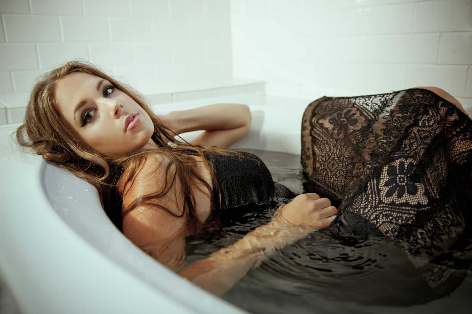 Shannon LaBrie in a bath in a black lace dress