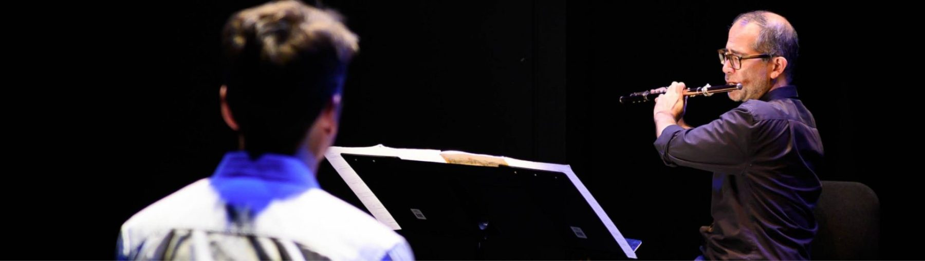 Mark Takeshi McGregor playing the flute for an audience member at As dreams are made