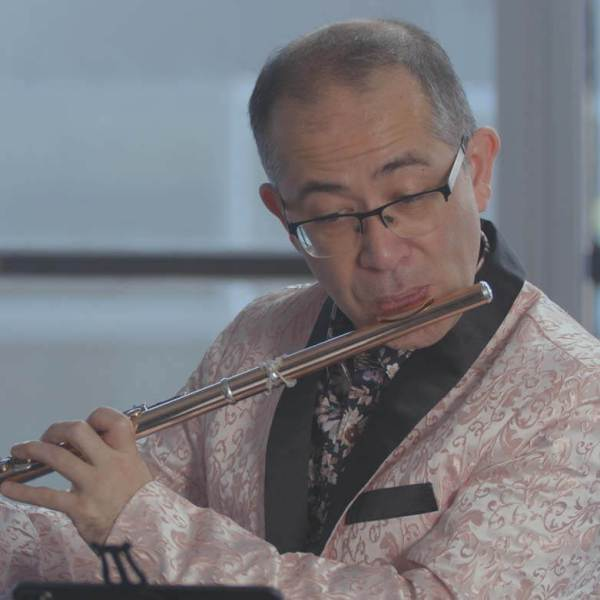 Mark Takeshi McGregor in a paisley pink jacket playing the flute