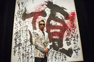 <写真>記者会見に臨んだ長渕剛、自筆の「てっぺん」披露