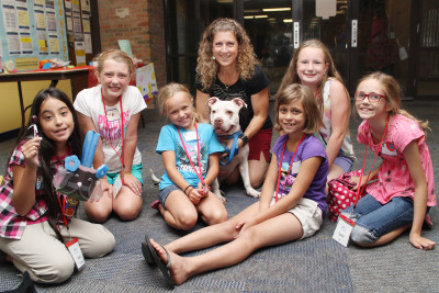 Licks for Puppies students pose with Pound Buddies director Lana Carson and Bella, an American Bulldog mix.
