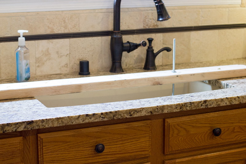 2 x 4 straddling the sink and anchoring the weight