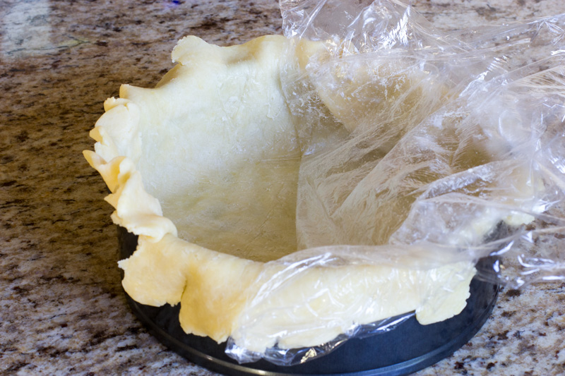 Demonstrating how to place the bottom crust by peeling plastic wrap