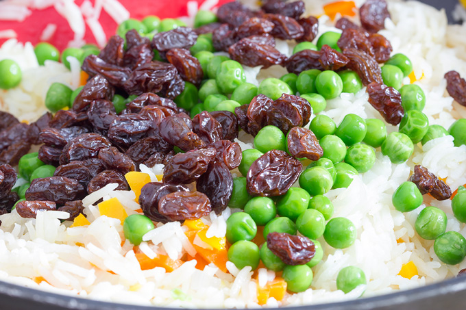 Adding raisins and peas to Greek rice