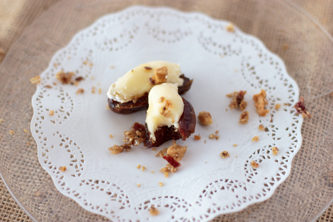 Two stuffed dates on a dish with fruit crisp garnish