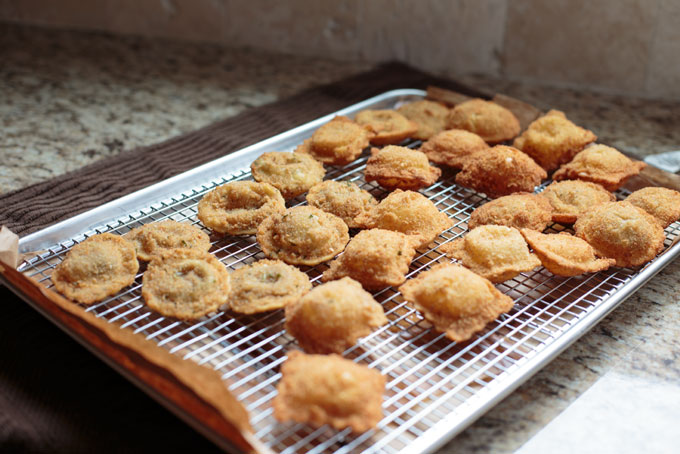 Fried ravioli draining on a cooking rack