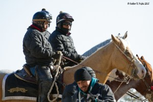 A few bundled up outriders patiently wait for horses to be done in the paddock area prior to a race at Hawthorne
