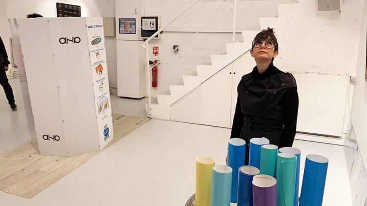 avant une séance de live painting, une femme debout derrière son matériel et devant son support artistique dans un loft tout blanc