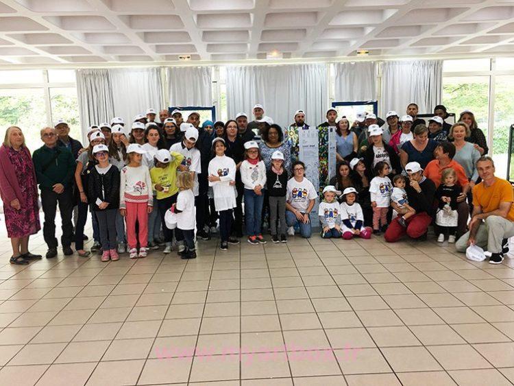 un groupe associatif parents enfants devant une fresque collective aNa MYARTBOX