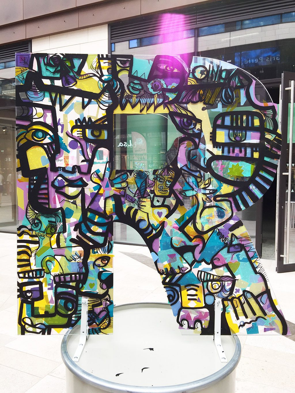 une lettre R géante décorées de couleurs et exposée sur un bidon en acier