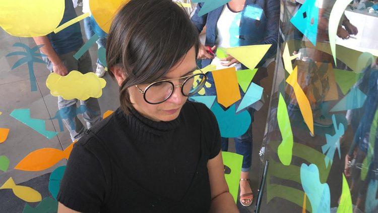 une femme vêtue de Noir portant des lunettes rondes peint dans un totem tube plexi