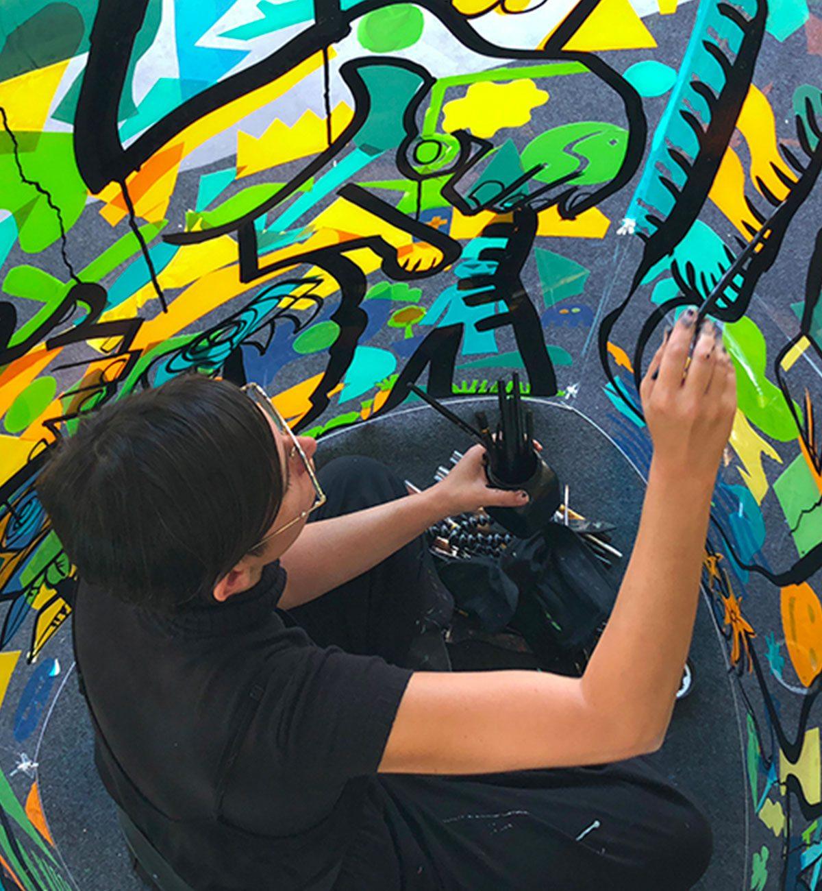 l'artiste de live painting aNa en train de peindre depuis le centre de son tube géant plexi art entourée de formes de couleurs jaunes vertes et bleues