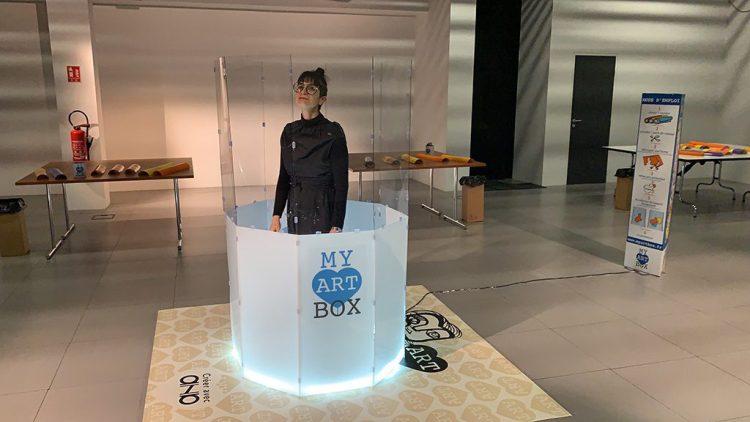 Une artiste se tient debout dans un tube cylindrique composée d'une partie haute totalement transparente et d'une partie basse blanche rétro éclairée et présentant le logo my art box bleu et gris