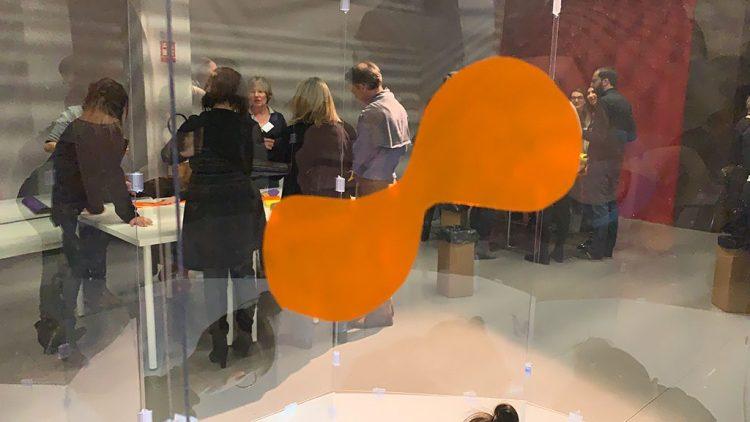 une forme simple orange découpée dans du vinyle collé sur le tube plexi transparent lors d'un atelier team building pour intéroger et surprendre à la manière de rené magritte