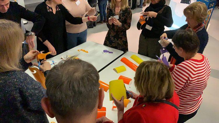Atelier team building créatif d'un groupe de collaborateurs rassemblés autour d'une table de travail et en train de découper des formes colorées dans des adhésifs à poser sur le tube fresque plexi art de l'artiste aNa pour my art box à Lyon