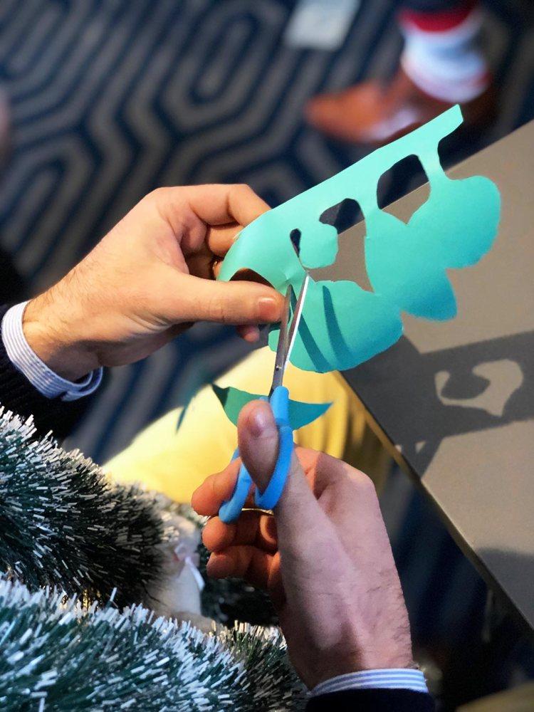 zoom sur les mains d'une personne en train de découper des formes originales dans du vinyle adhésif en atelier fresque my art box sur le principe du poisson d'avril